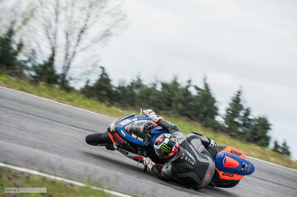 אופנוע מירוץ צבעוני בהחלקה על צידו השמאלי ורוכב שעדיין נטחז בו, רקע עצים ומסלול