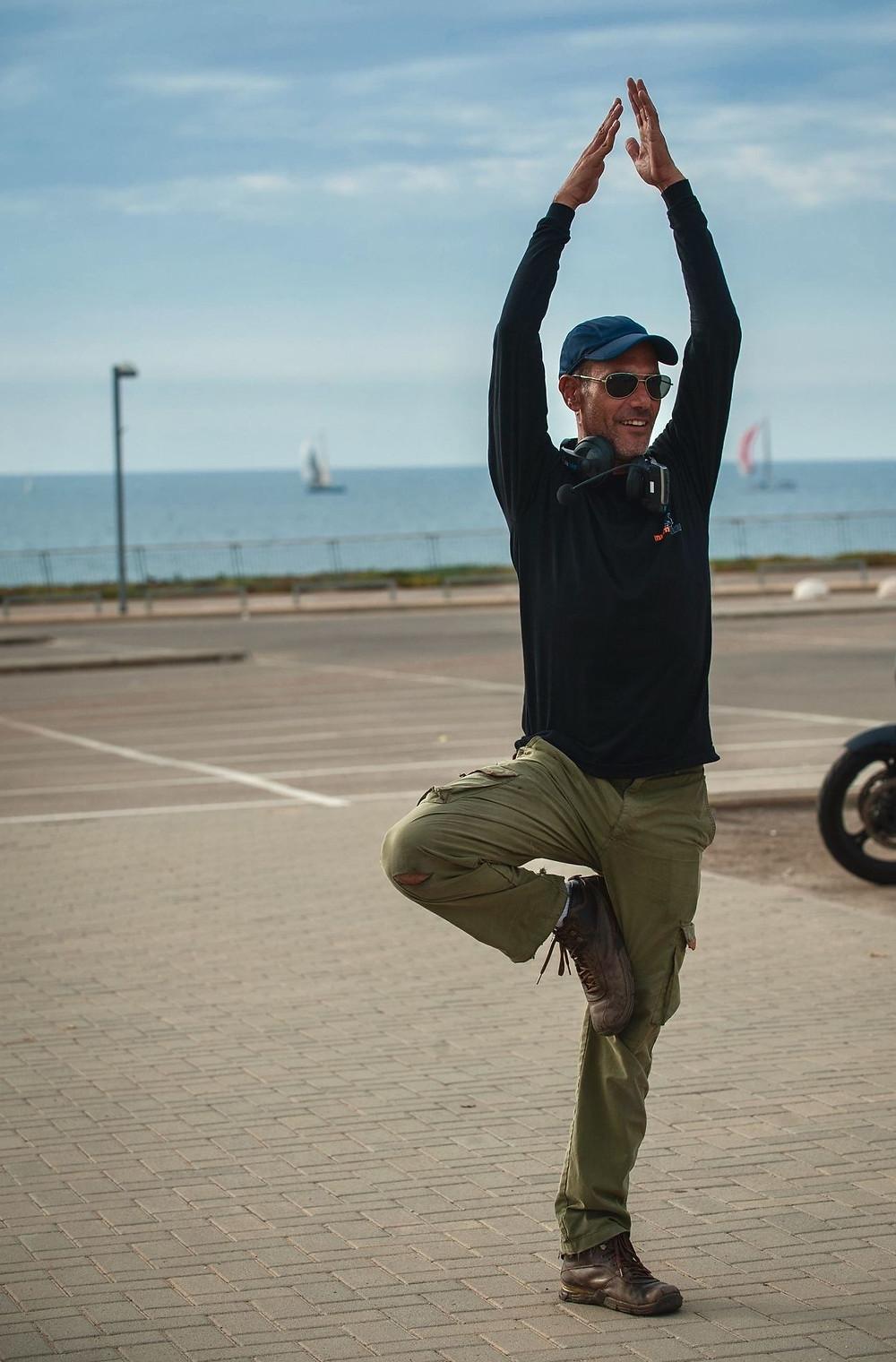 אדם עומד על רגל אחת בעמידת יוגה עם ידיים באוויר. ברקע מגרש חניה וים עם שתי סירות מפרש