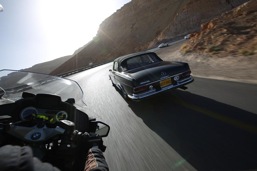 מבט מעבר לכתף של רוכב על אופנוע ב.מ.וו על כביש מדברי באור שמש ישירה ומרצדס עתיקה