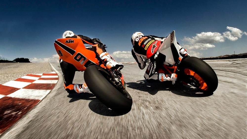 אופנוע כתום לצד אופנוע לבן מצלולמים מאחור במסלול מרוצים עם אבני שפה צבועים אדום ולבן