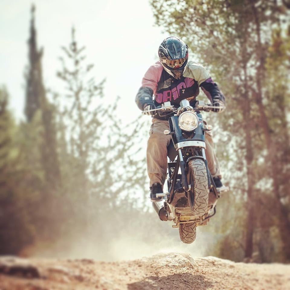 קטנוע קופץ באוויר על סלע בשביל בין עצים