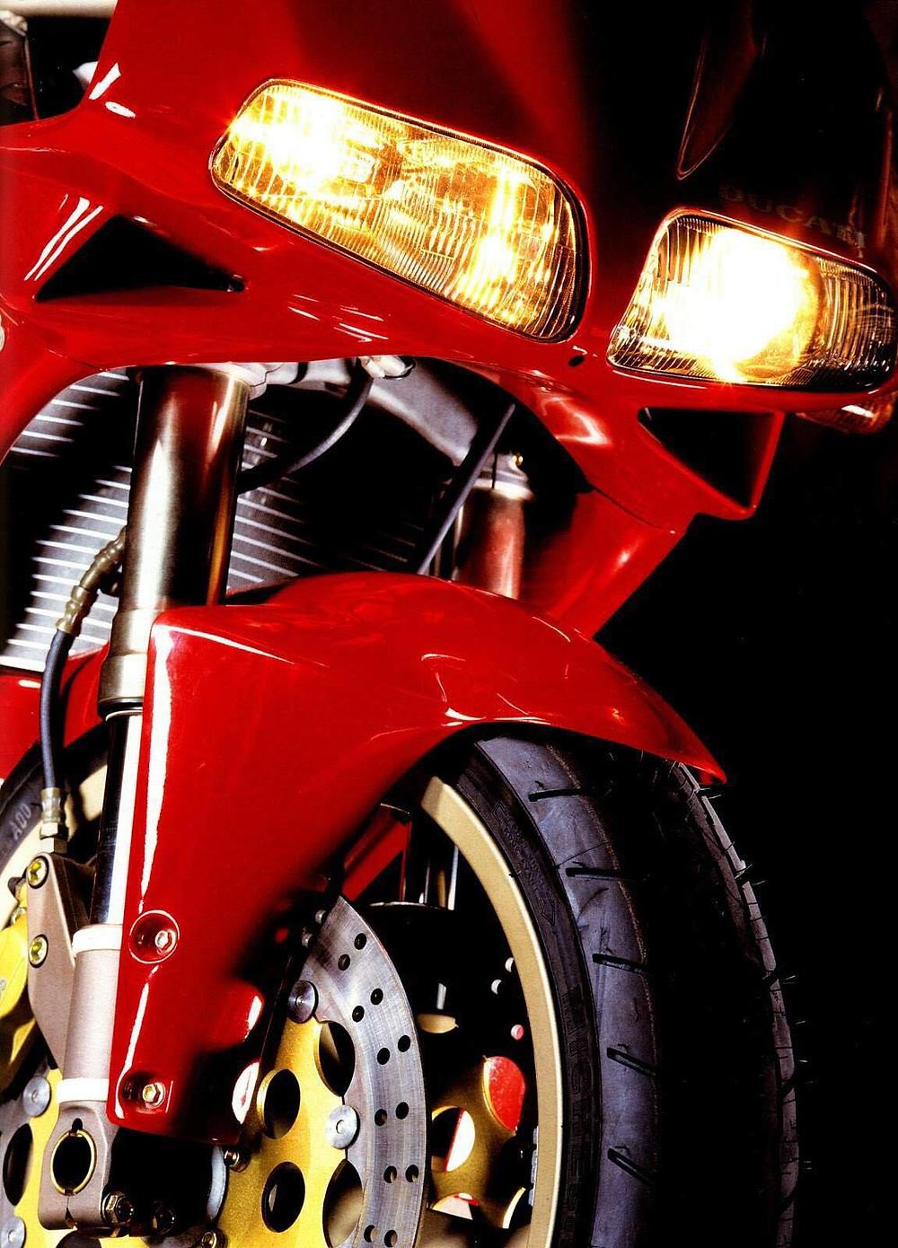 תמונת תקריב פנסים וגלגל קדמי אופנוע. דוקאטי 916 אדום.