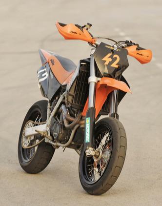 אופנוע קטמ סופרמוטו מספר 42 בתמונה סטטית ברקע אספלט