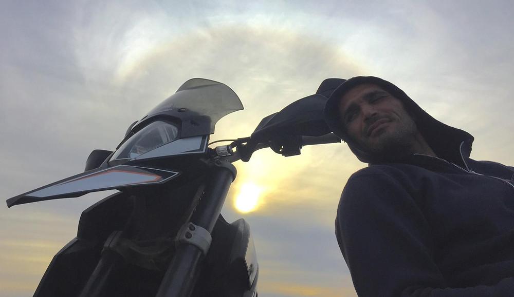 איש נשען על אופנוע ברקע שמיים עם אור שמש מאחורי עננים