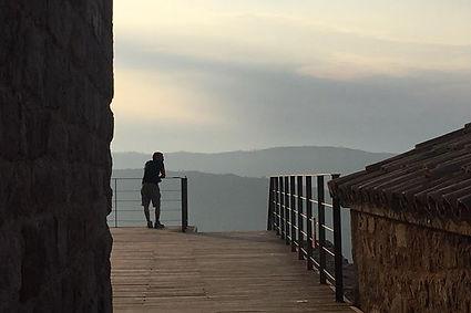 אדם מסתכל על נוף הרים וזריחה ממרפסת עתיקה