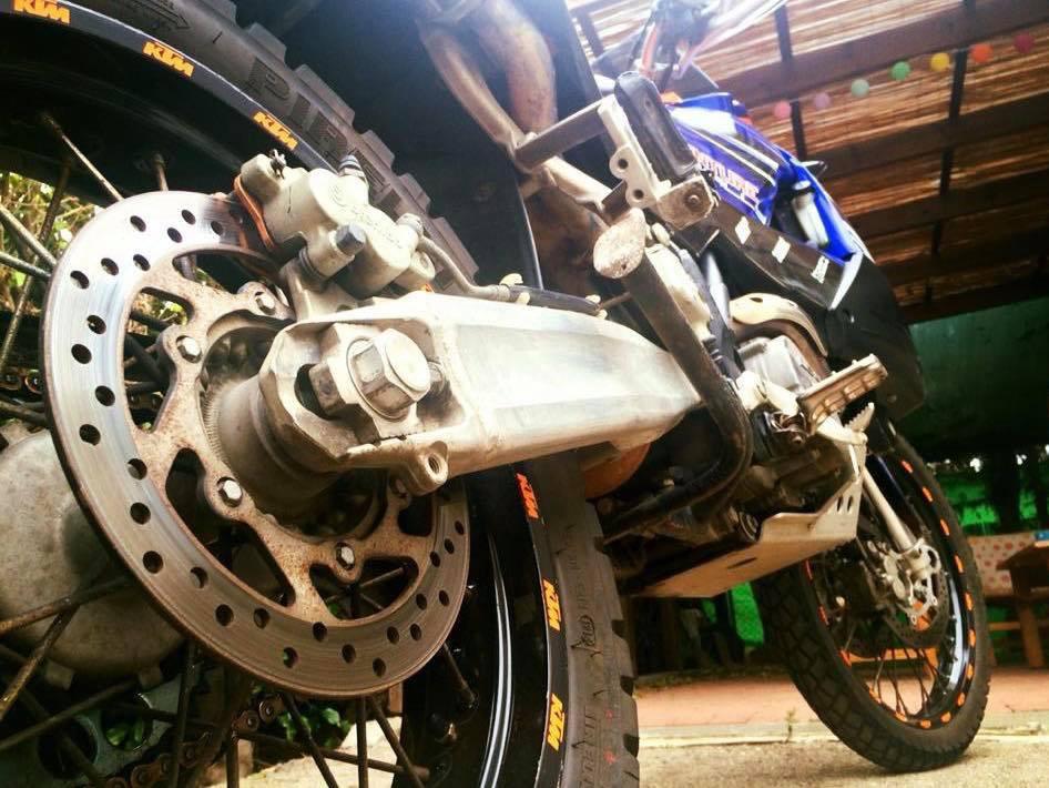 אופנוע מצולם מכיוון הגלגל האחורי ברקע סככה
