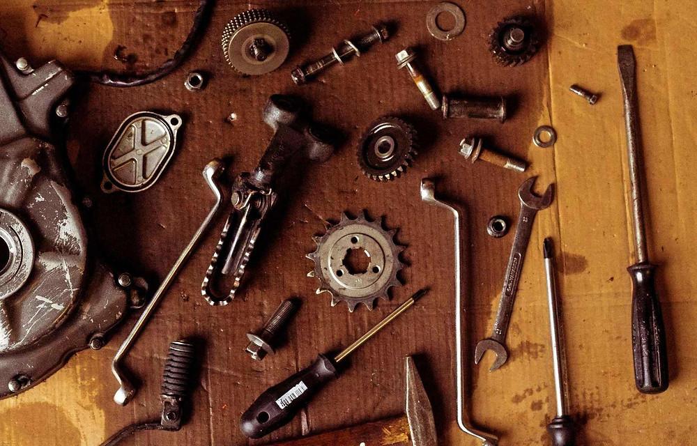 כלי עבודה וחלקי אופנוע מונחים על קרטון ספוג שמן