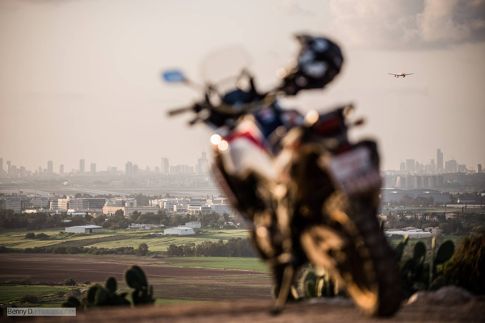 אופנוע מטושטש ברקע שדות וביניינים רחוקים, מטוס עף בשמיים