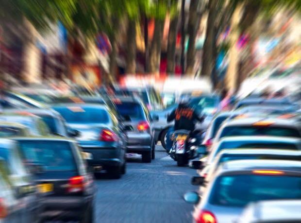 אופנוע בין תנועת רכבים עמוסה, תמונה מטושטשת בצדדים.