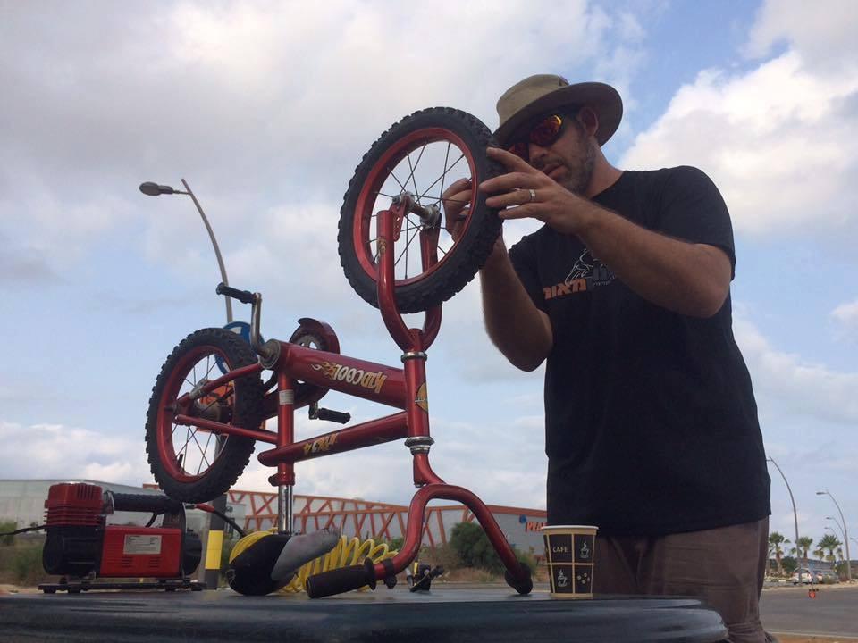 אופניים הפוכות על שולחן מקבלות טיפול לגלגלים