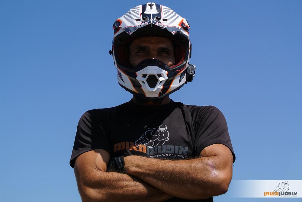 רוכב אופנוע עם קסדץ שטח, לוגו 'אופנוען מאומן' על החולצה ובסימן מים