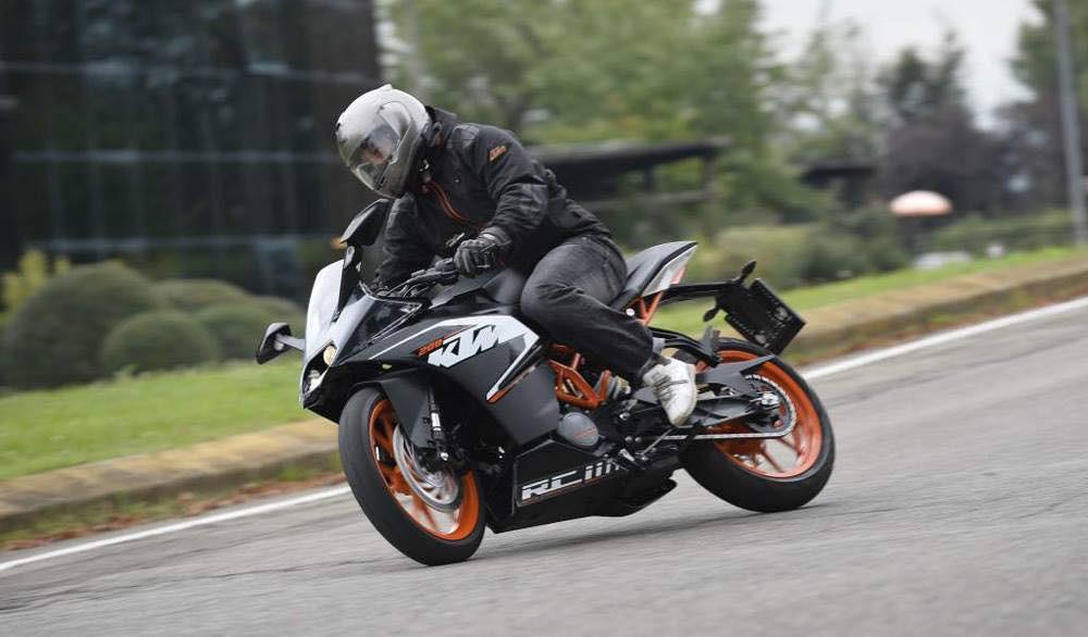 אופנוע ספורט שחור כתום של קטמ מחליק אחורי על אספלט ברקע דשא ובניין משרדים