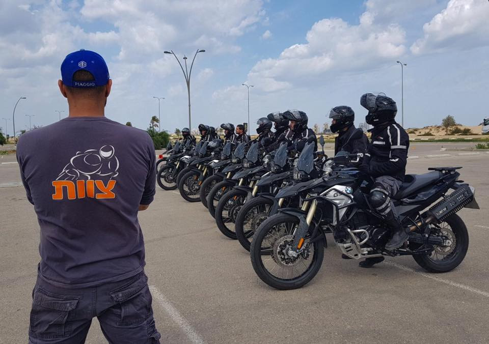 שורת אופנועים משטרתיים על מגרש עם רוכבים, גב של איש צוות שמשגיח מהצד