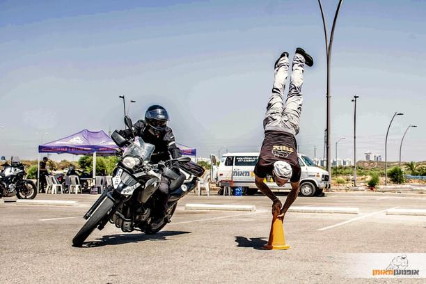 אופנוע מטרתי בהטיה במגרש סביב קונוס ואדם בעמידת ידיים על הקונוס, אופנוען מאומן