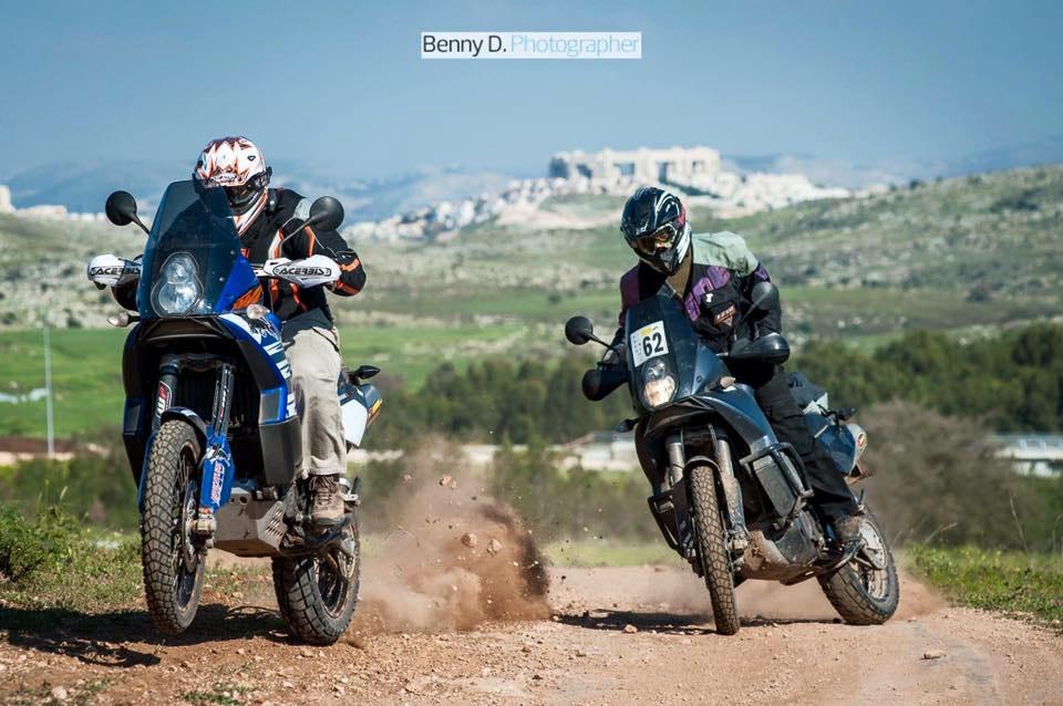 שני אופנועים באקשן על שביל ברקע הרים מסלועים וישוב מרוחק