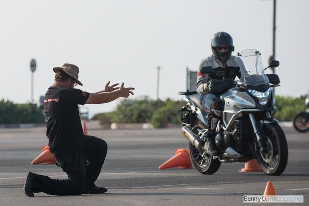 רוכב על אופנוע במגרש בין קונוסים ואדם עם כובע קורע ברך ושולח ידיים לפנים לצידו