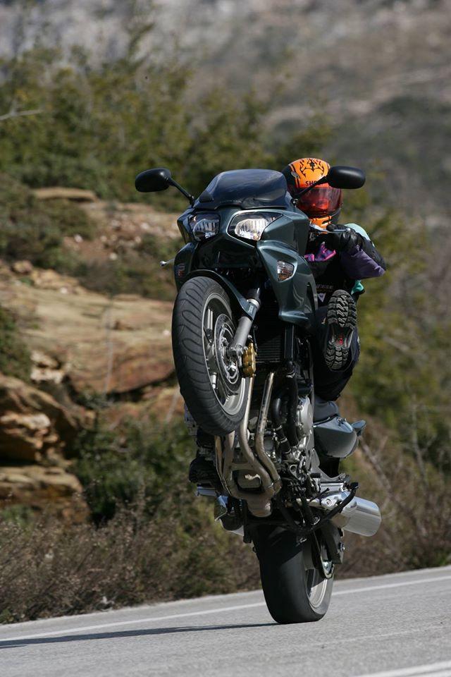 אופנוע על גלגל אחד, רוכב עם קסדה כתומה מביט במראה