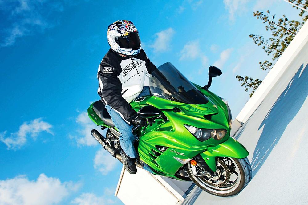 אופנוע ירוק מנצנץ פרונטלי בסטופי ברקע שמיים כחולים עם עננים ומבנה לבן