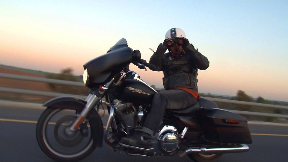 הארלי דווידסון על הכביש ברקע שקיעה, רוכב מביט למצלמה דרך משקפת בלי ידיים על הכידון
