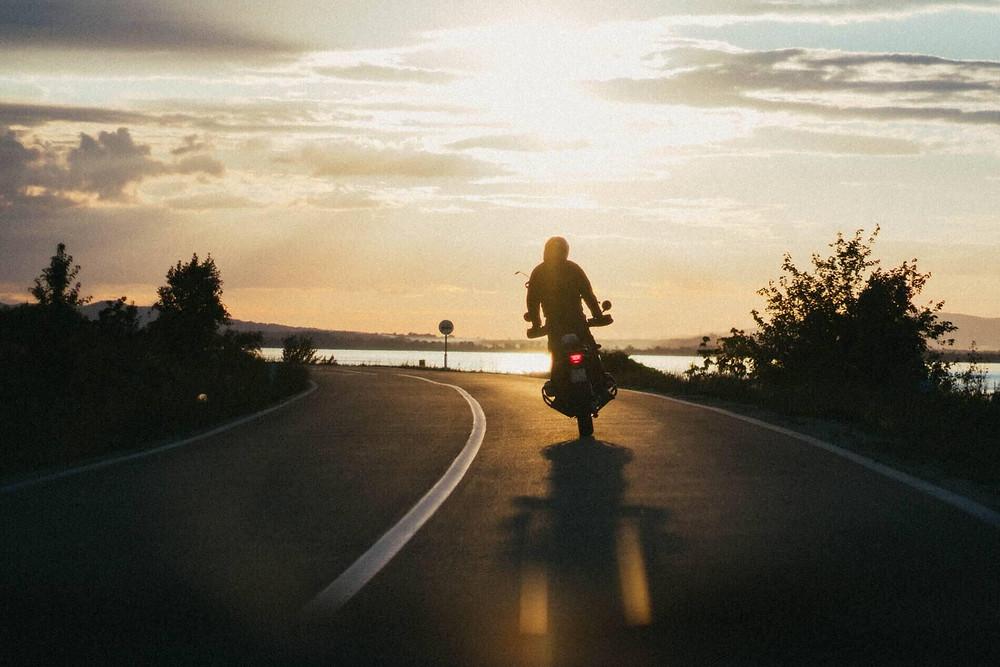 צללית של אופנוע עם רוכב בעמידה נוסע לעבר השקיעה, החזר אור מהכביש ושמיים עם עננים ברקע