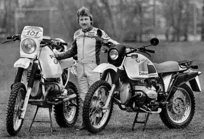גסטון רייהר עומד בין אופנוע הראלי שלו לבין אופנוע בייצור סדרתי, רקע עצים ודשא, שחור לבן