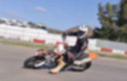 רוכב בחליפת עור על אופנוע סופרמוטו בהשכבה במסלול
