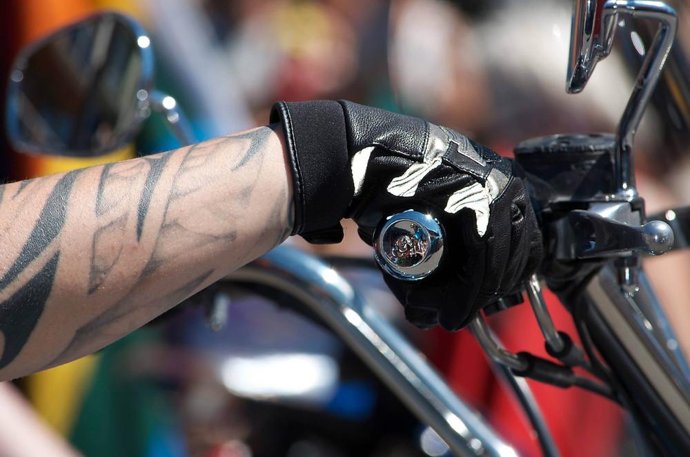 יד מקועקעת אוחזת ידית גז של אופנוע, רקע מטושטש וצבעוני