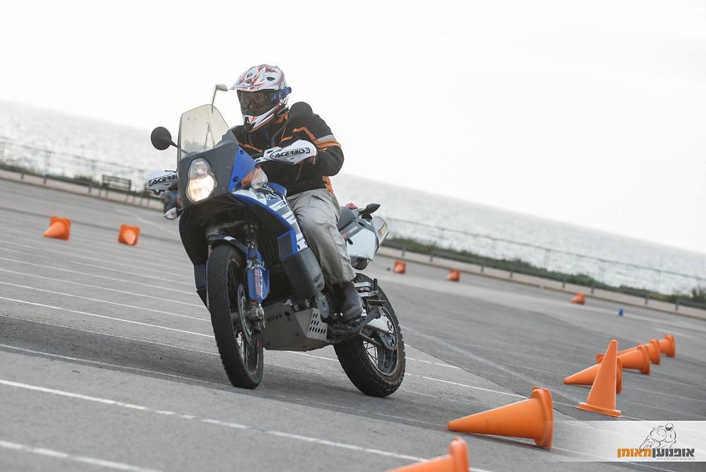 אופנוע כחול בהטיה עם זנב בצד על מגרש חניה מלא קונוסים ליד הים