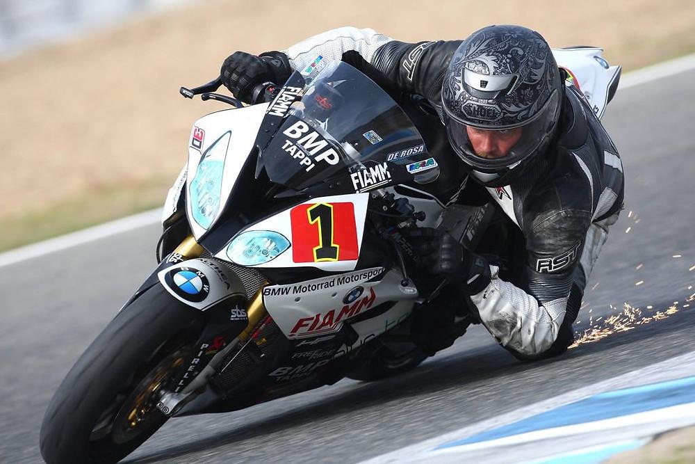 אופנוע ספורט של במוו במסלול מירוצים, רוכב משייף ברך ומוציא ניצוצות