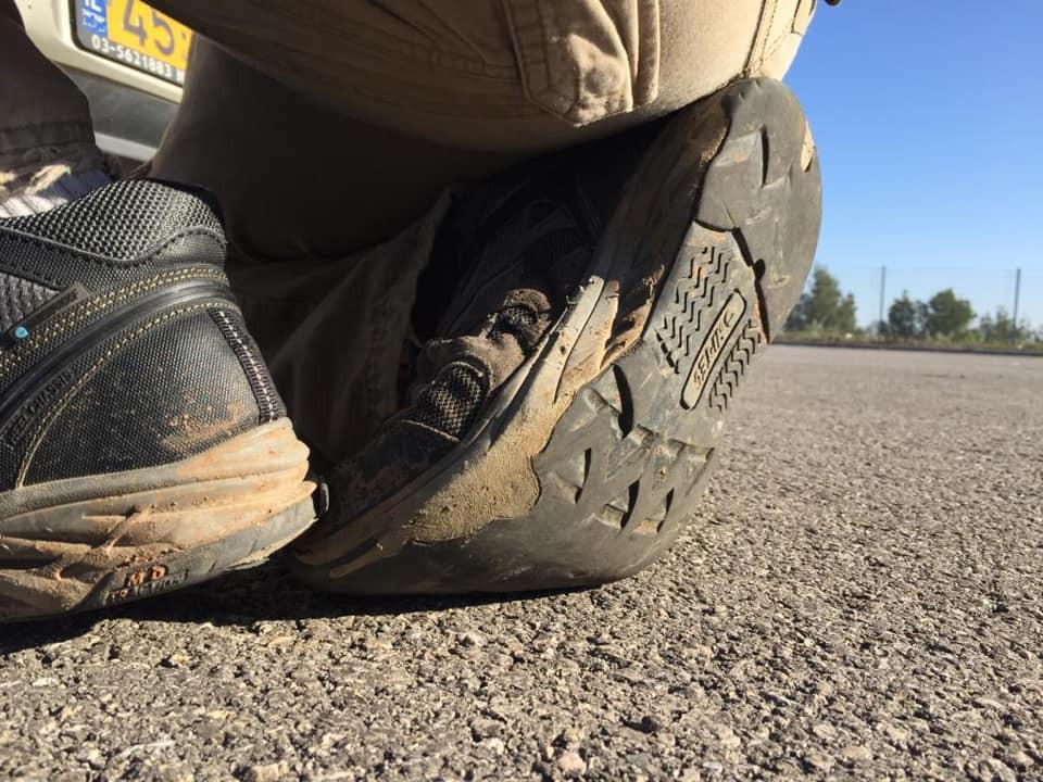 נעליים עם סוליות שחוקות על רקע אספלט ועצים רחוקים