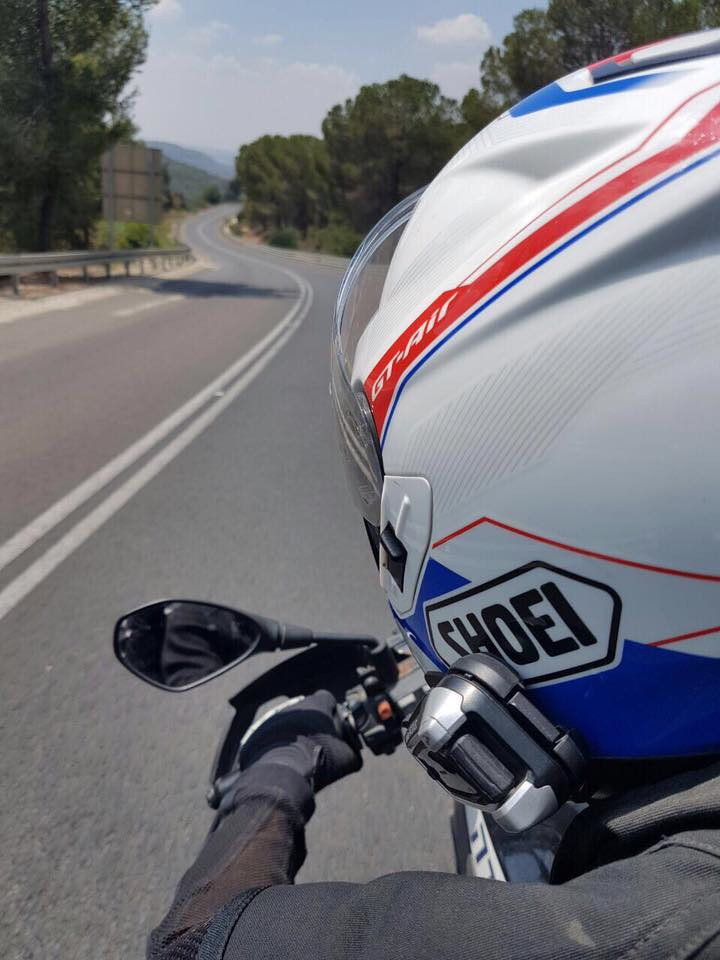 מבט מאחור אל קסדת אופנוע וכביש שמתפתל אל האופק ברקע עצים