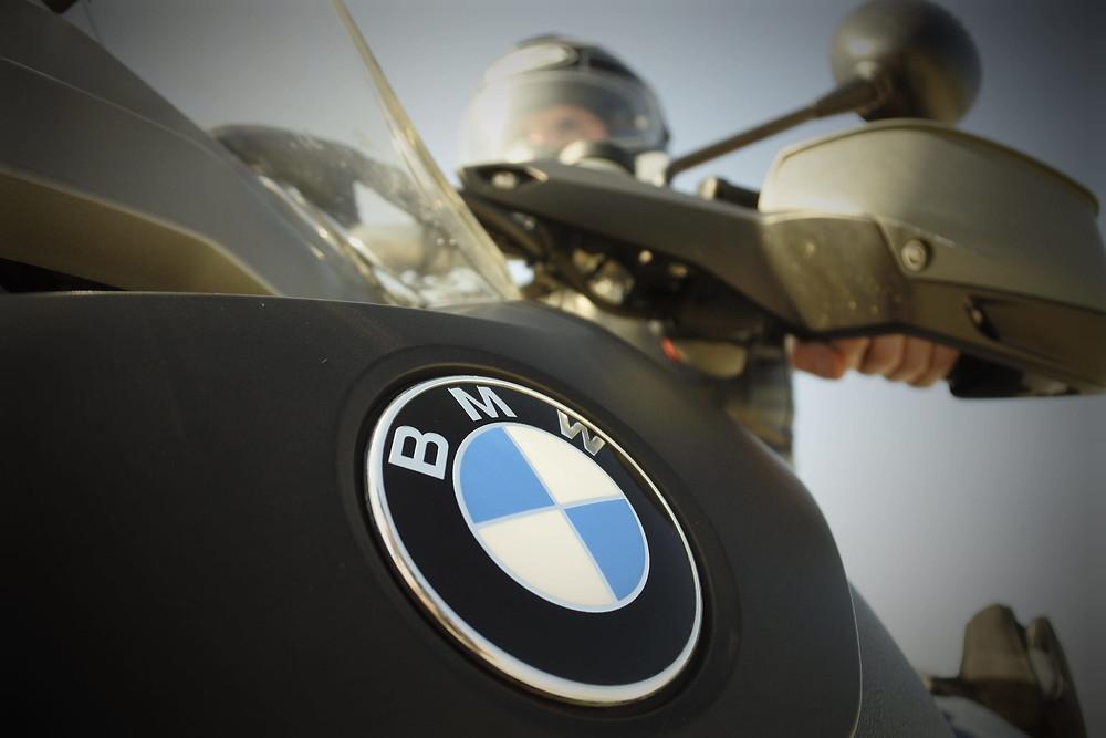 סמל במוו על אופנוע מצולם מלמטה בזווית רחבה, רוכב עם קסדה אוחז בכידון ברקע