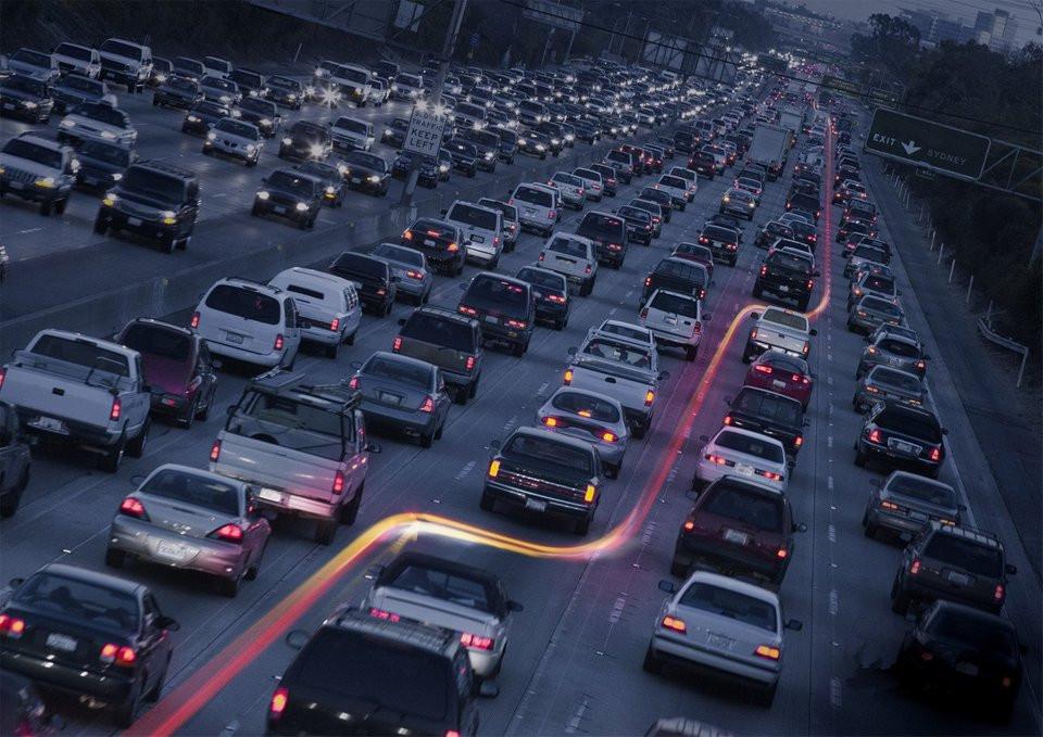 תאורת אופנוע חותכת דרך תנועת רכבים כבדה