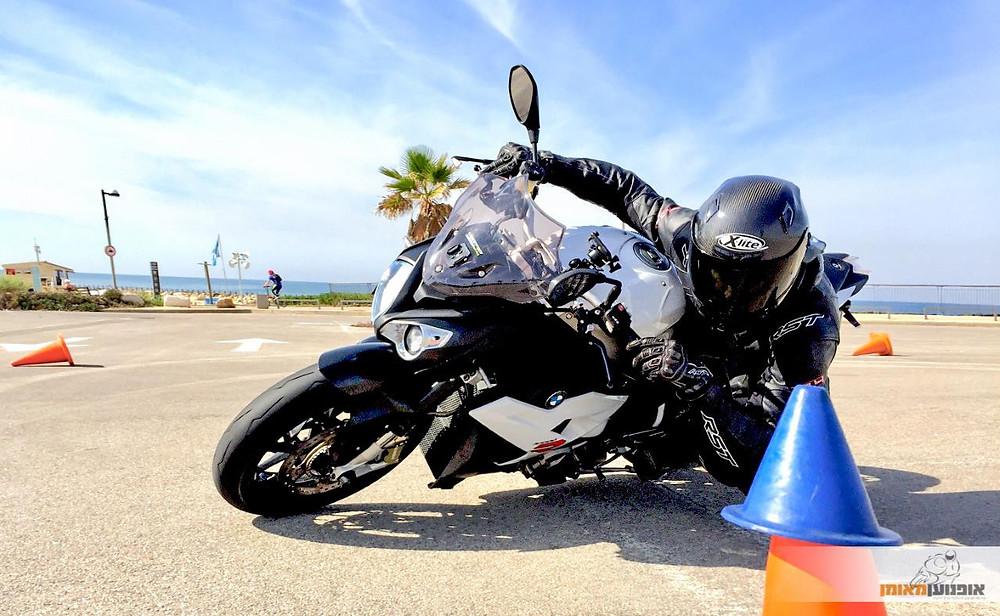 אופנוע במוו לבן, מגרש, קונוסים, שמיים כחולים עם עננים, ים
