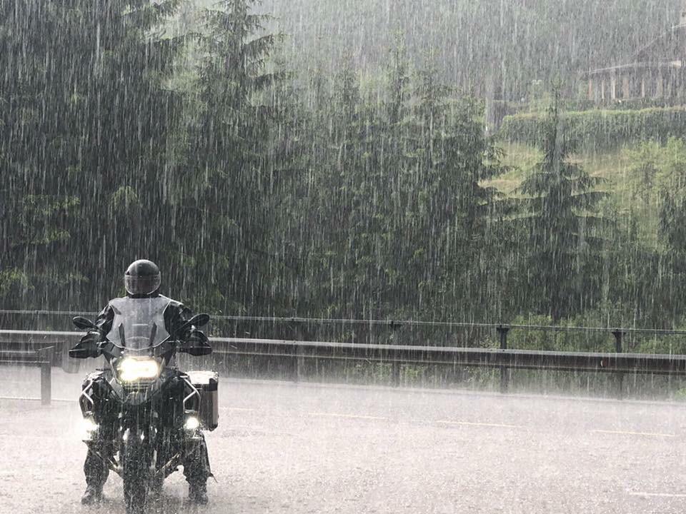 רוכב על אופנוע r1200gs עומד בגשם ברקע עצים,גדר ובית.