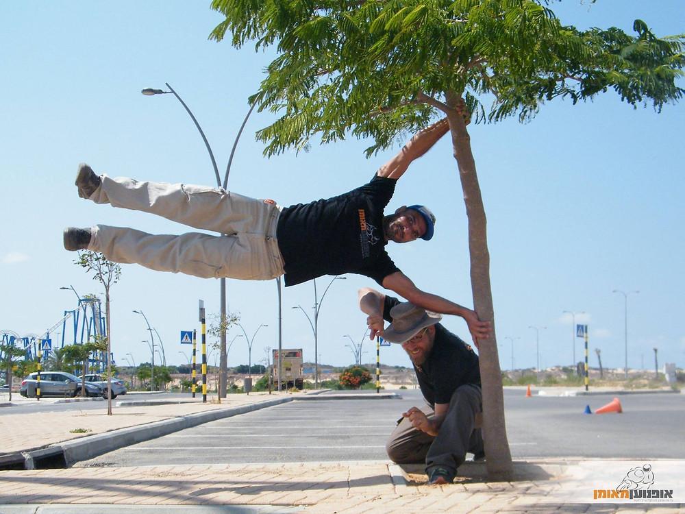 אדם נתלה על עץ על הצד ומתחתיו אדם נוסף קורע ברך, מגרש חניה ברקע, אופנוען מאומן
