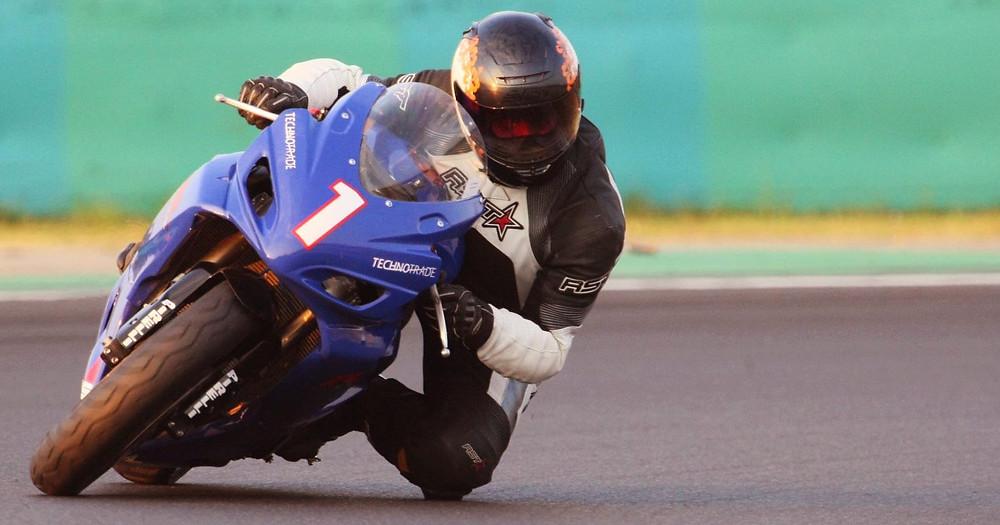 אופנוע כחול עם לוחית מספר 1, רוכב עם ברך באספלט