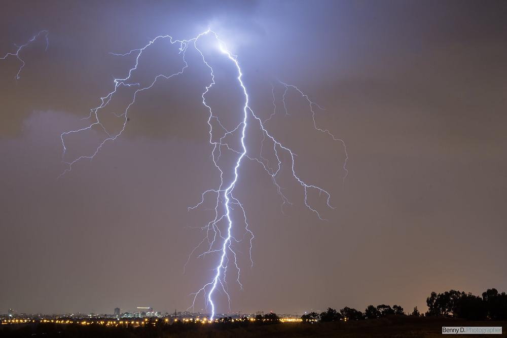 הבזק ברק מהשמיים שפוגע באדמה בחשיכת לילה. אורות דרך וישוב מרוחק ברקע.