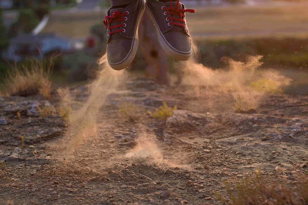 זוג נעליים בקפיצה באוויר על אדמה, מפזרות אבק לצדדים