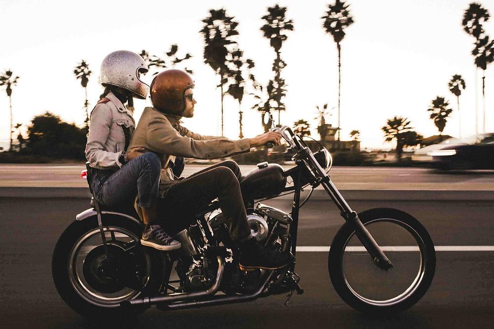רוכב ומורכבת על האופנוע קאסטום ברקע עצי דקל