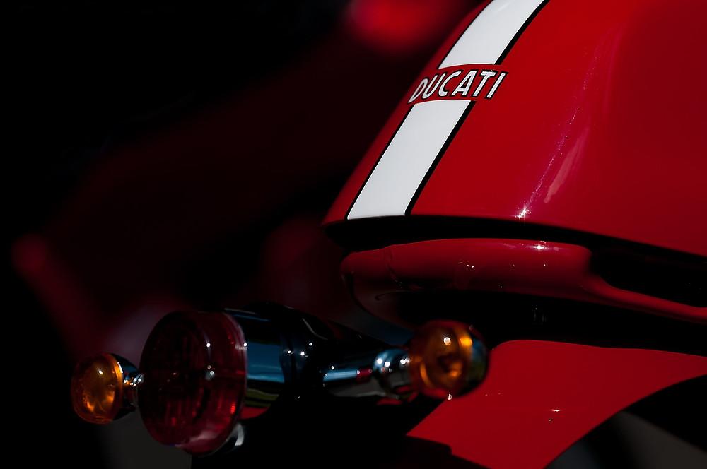 פנסים אחוריים וזנב של אופנוע אדום לבן עם כיתוב דוקאטי ברקע שחור
