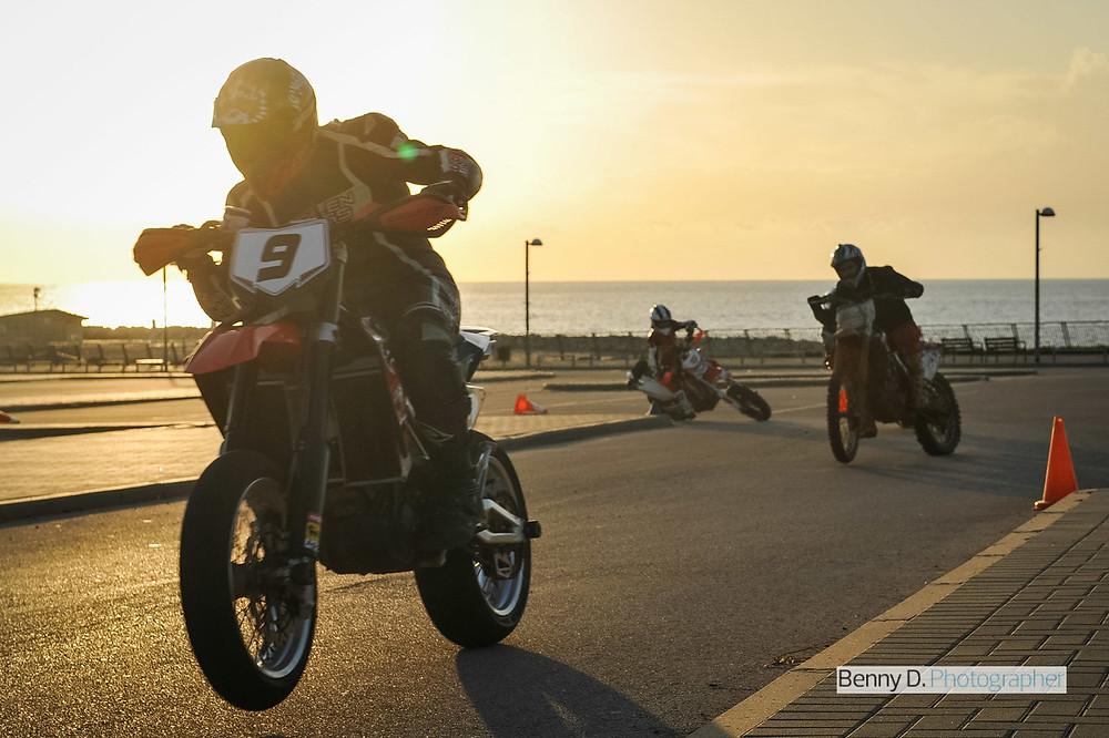 שלושה אופנועים נוסעים במגרש אימונים בין קונוסים ברקע ים ושקיעה