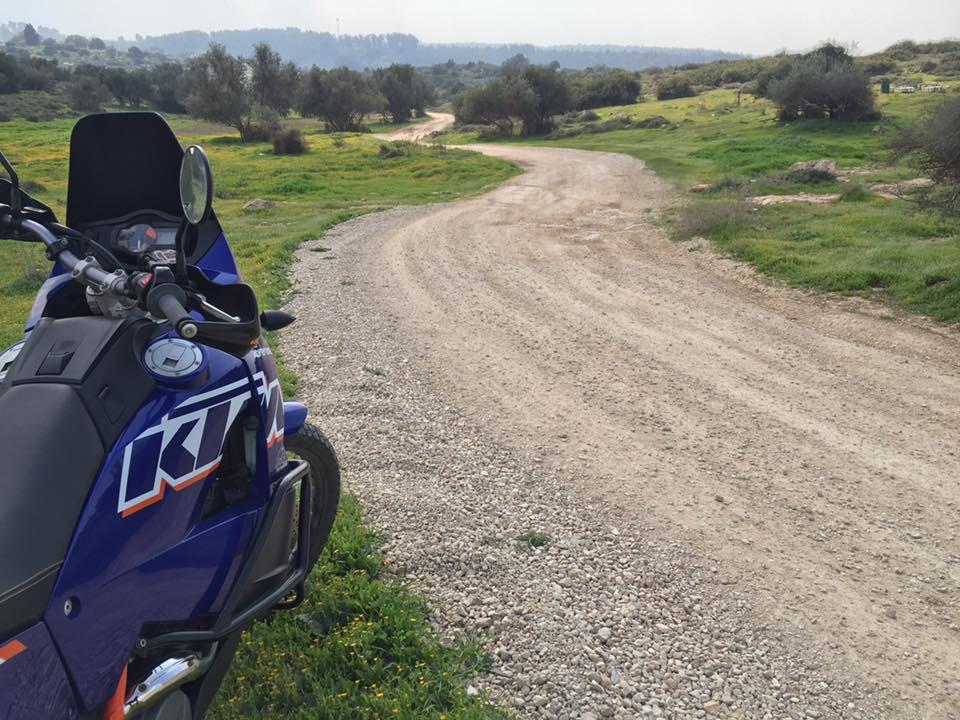 אופנוע כחול עומד בצד שביל שמתפתל בין עשב ועצים עד האופק