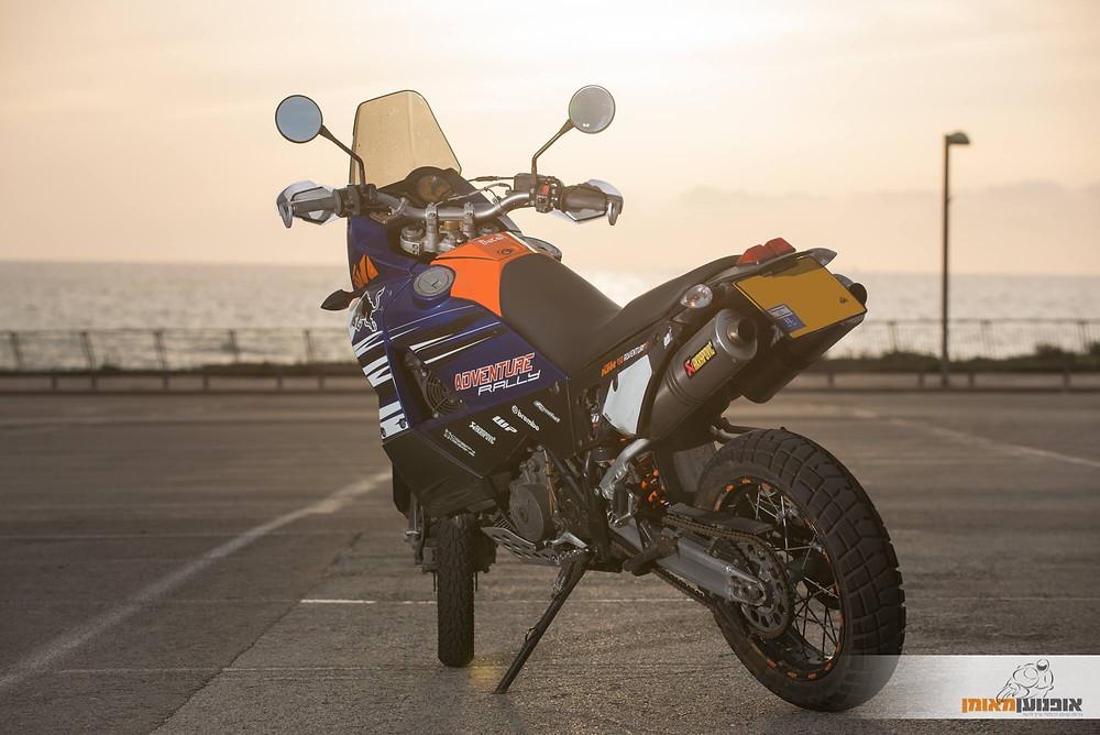 תמונה סטטית של אופנוע על מגרש חניה ברקע טיילת ים ושקיעה