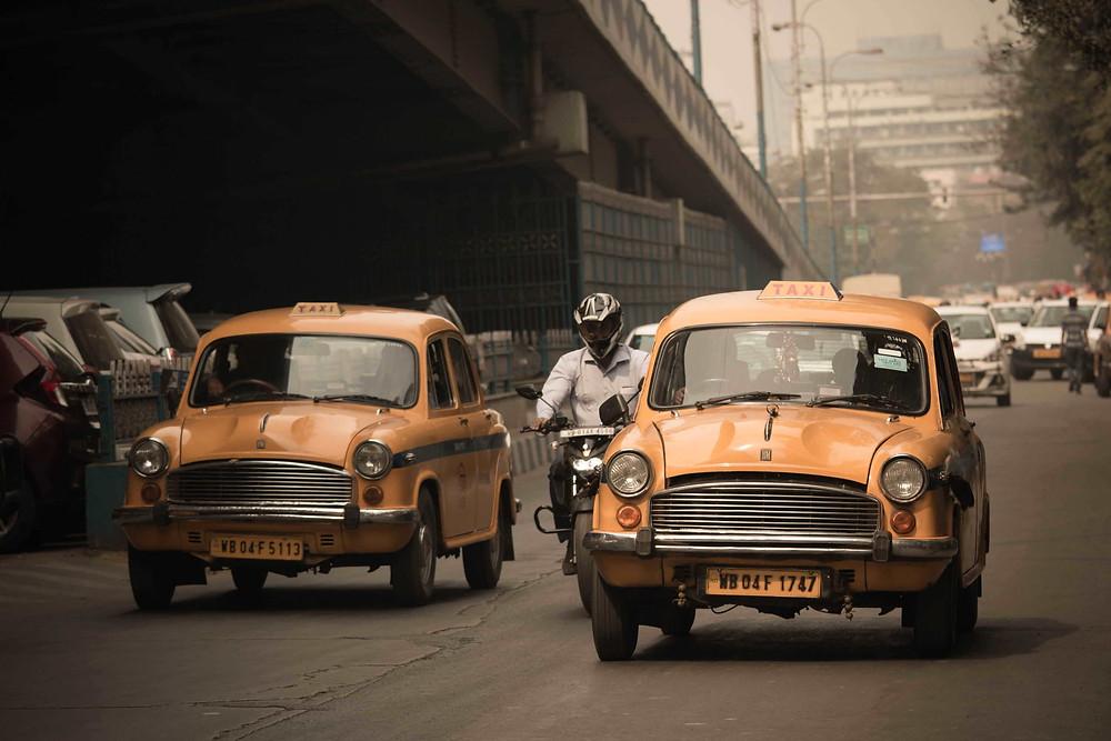 אופנוע עובר בין שתי מוניות צהובות, ברקע גשר ותנועת כלי רכב