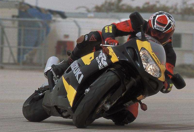 אופנוע בסלייד על הברך, רוכב גידי פרדר למגזין מוטו בחליפה אדומה, רקע מחסנים וגדר, סוזוקי R750