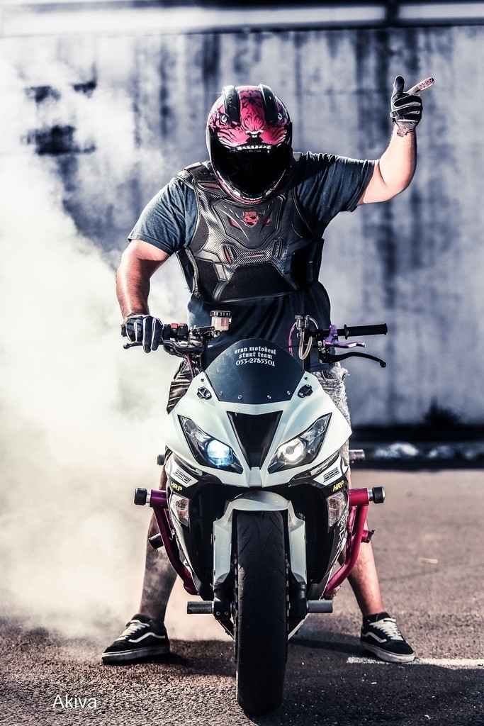תמונה פרונטלית של אופנוע, ברן אווט, רוכב מצביע לאוויר, קסדה ורודה, רקע תעשייתי