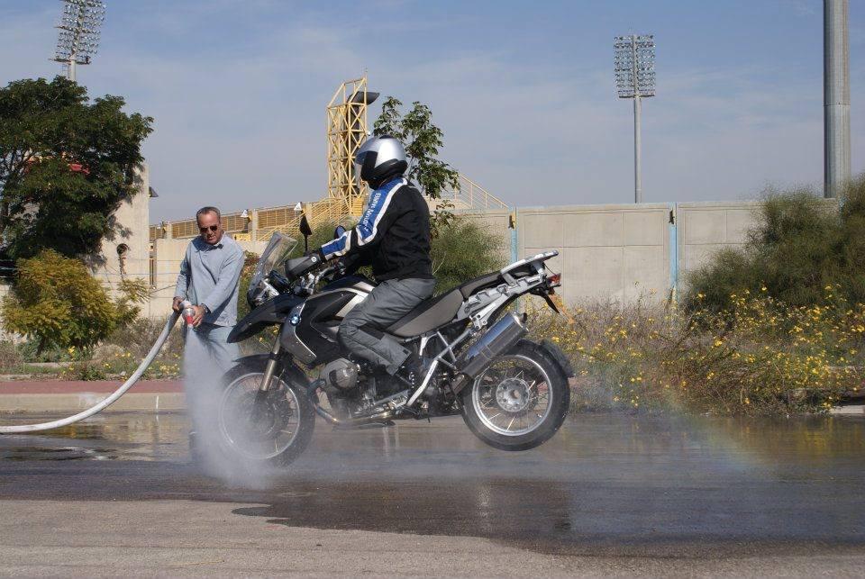 bmw r1200gs. סטופי על מגרש רטוב. איש משפריץ מים על האופנוע והמגרש.