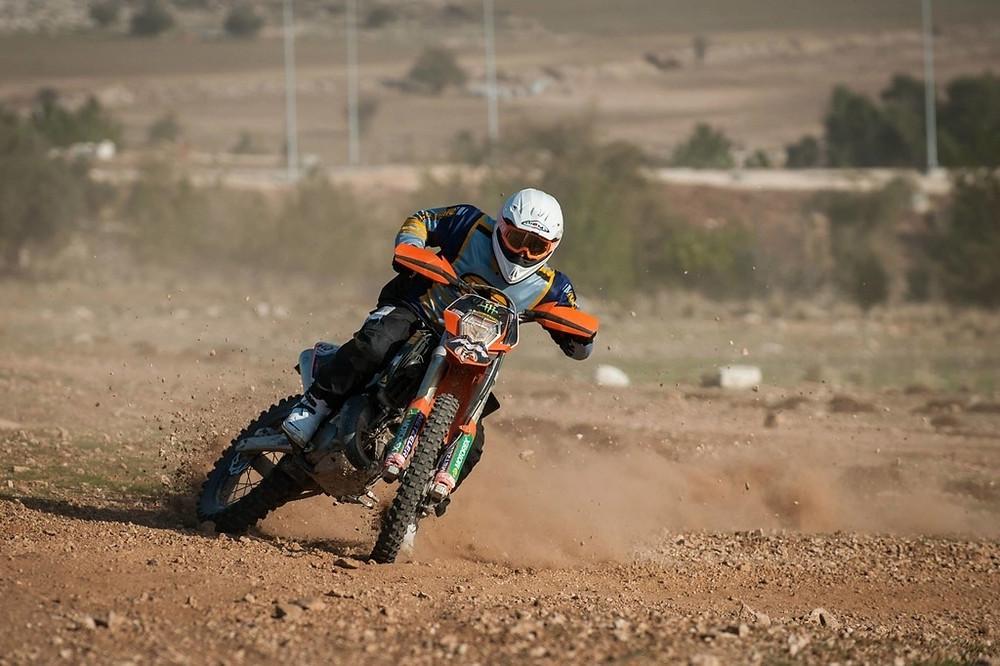 אופנוע אנדורו כתום בהחלקה על הגז בשטח, רקע חום ואדמה