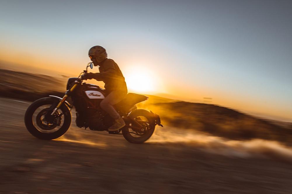 אופנוע אינדיאן נוסע בעפר, שקיעה ברקע הרים, שובל אבק